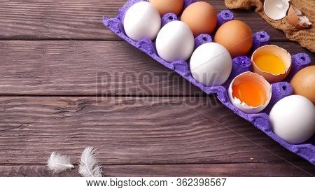 White And Brown Chicken Eggs In Tray And Two Eggs Broken In Which Yolks Of Different Colors Are Visi