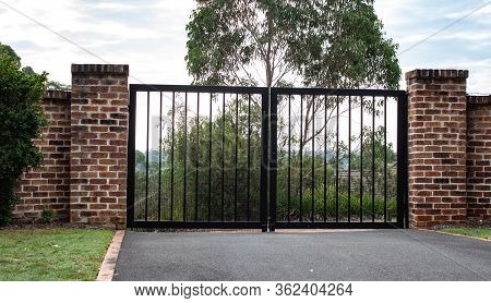 Black Metal Wrought Iron Driveway Property Entrance Gates  Set In Brick Fence, Lights, Green Grass,