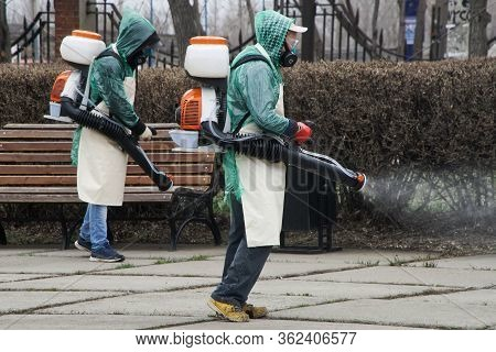 Two Men In Protective Suits Decontaminate A City Square Or Street During Quarantine And A Pandemic.