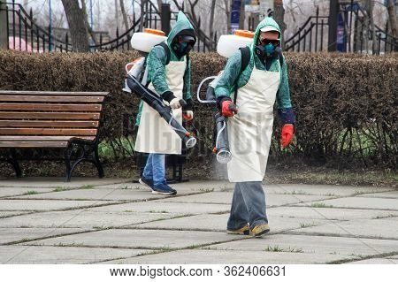 Workers In Chemical Protection Suits Decontaminate A City Street Or Park During Quarantine And A Pan