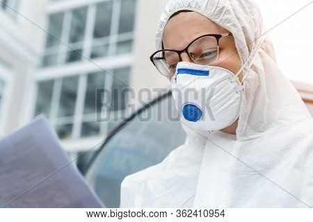 Portrait Of Tired Exhausted Female Doctor, Scientist Or Nurse Wearing Face Mask And Biological Hazma