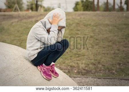 Upset Sad Depressed Little School Girl Sitting Alone At City Street Park Clutching Head. Upset Stres