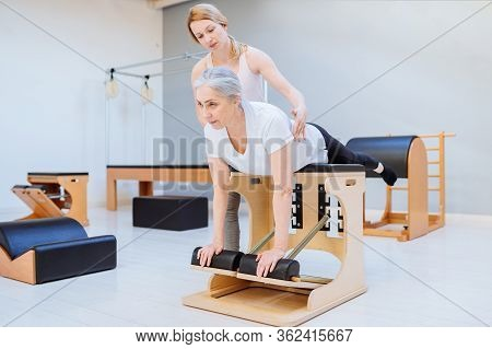 Woman Woman Doing Pilates On The Pilates Cadillac, Supporting And Helping Her Positive Young Woman I