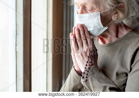 An Elderly Woman In A Medical Respiratory Mask Near The Window Prays With A Rosary And A Cross. Pray