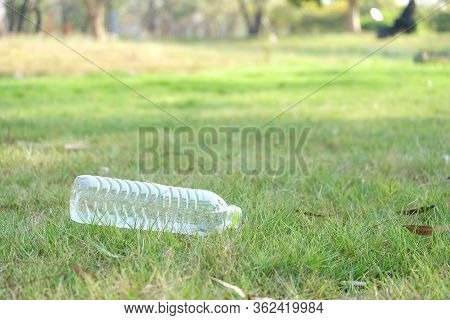 A Plastic Trash Bottle Of Drinking Water Littering On Green Grass Field At The Park With Nature Back