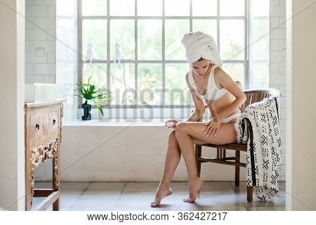 Young Adult Girl With Towel On Head Sitting On Chair In White Bathroom, Applying Soft Natural Cream