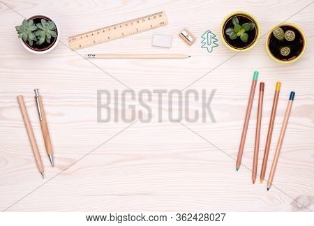 Desk top with eco friendly office supplies such as wooden pen, pencils and small plants with copy space