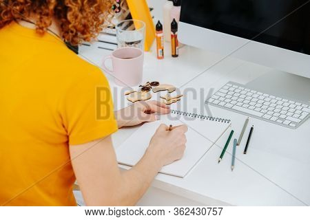 Artist Woman Drawing Behind Work Desk In Her Notepad With Crayon. From Behind