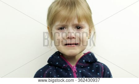 Portrait Of Little Toddler Girl Crying With Tears On Her Eyes. White Background. Childhood Concept.
