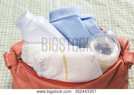 Close Up Of Small Pink Diaper Bag On Changing Pad. First Care Baby Accessories With Bottle. Soft Gre