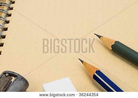 Two Wooden Pencil, Eraser And Sharpener On Recycle Notebook Background.