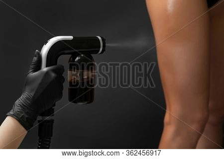 Master Applies Liquid Tan Spray For Professional Athlete Woman Using Airbrush In Beauty Salon