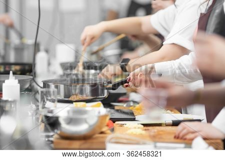 Background Cook Leads Master Class In Cooking In Kitchen