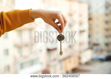 Woman Holding Key From New Apartment Over Construction Background. Real Estate Concept. Hand With Ho