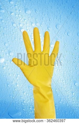 close up hand wearing yellow cleaning gloves over water drops covered background