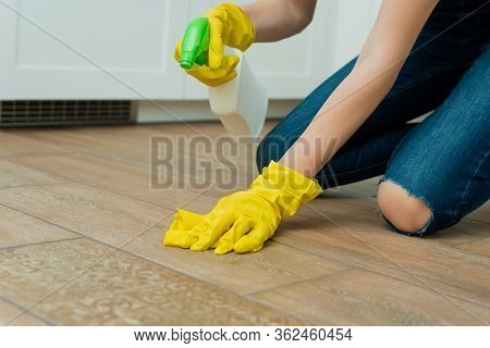 A Girl Is Washing A Floor In Yellow Gloves. A Girl Is Cleaning A Room With Detergents.