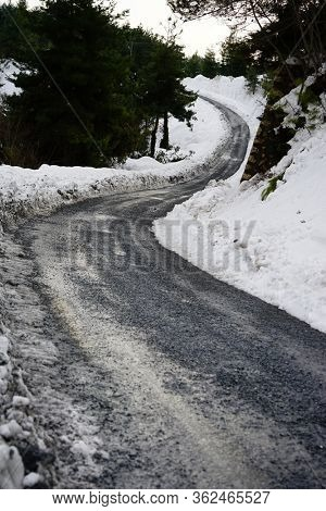close up snow covered mountainside empty road