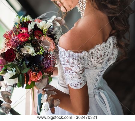 The Bride Wview From Back Keep The Bouquet. Art Bouquet. The Bride Stand Near The Winow In Wedding D