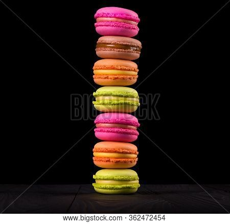 Stack Of French Colorful Macaroons On Wooden Table Isolated On Black Background