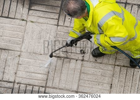 Worker Cleaning A Sidewalk With Pressurized Water. City Cleaning Or Maintenance Concept. Top View