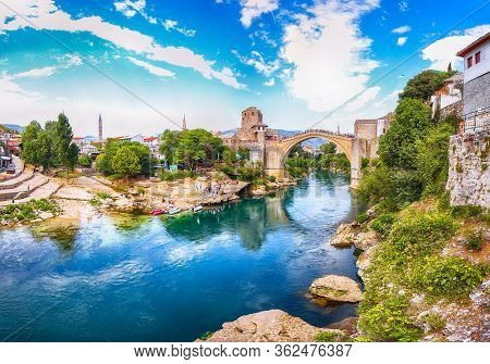 Fantastic Skyline Of Mostar With The Mostar Bridge, Houses And Minarets, During Sunny Day. Location: