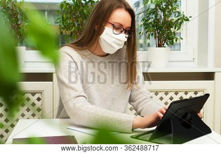 Woman In Glasses And Mask Works From Home. Quarantine Concept.