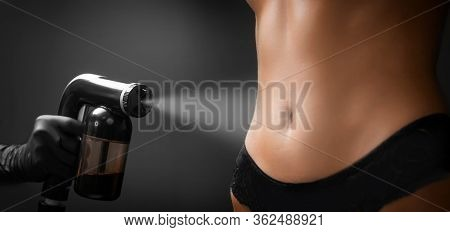 Woman Body Paint With Airbrush Spray Tan In Professional Beauty Salon On Black Background