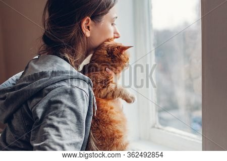 Isolation At Home During Coronavirus Covid-19 Pandemic. Woman Looking At Window With Cat. Stay Safe