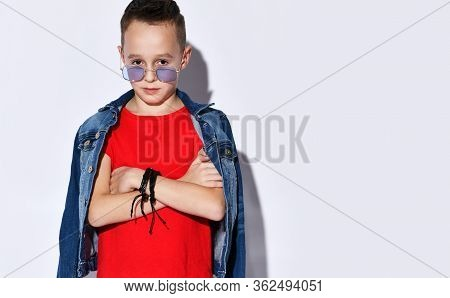 Teenage Kid With Stylish Hairstyle, In Purple Sunglasses, Red T-shirt And Denim Jacket, Black Bracel