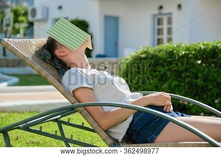 Tired Teenager Student Asleep On Sunbed With Book. Sleeping Girl On Sunny Day, On Green Lawn In Gard