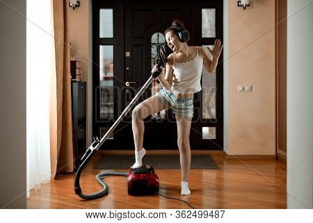 Girl Having Fun While Cleaning In Big Headphones And Singing In A Brush From A Vacuum Cleaner