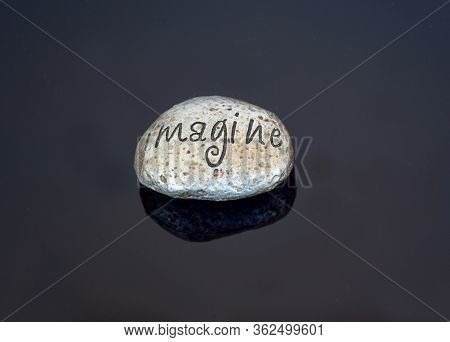 Painted Rock Imagine Word On A Shiny Black Background.  The Rock Is A Metallic Silver Color, Great F