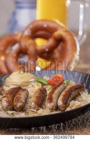 Grilled Nuremberger Bratwurst With Sauerkraut On Wood