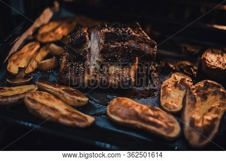 Roast Pork Belly With Potatoes On Baking Tray Cooked In Oven. Traditional Country Cuisine. Baked Fat
