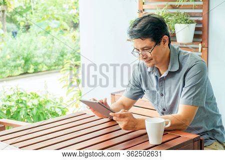 Middle Age  Man Sitting In The House And Using   Tablet For Online Working At Home For Self Quaranti