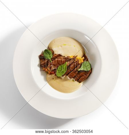 Beef heart ragout and vegetables. Served roasted meat with veggies risotto in plate isolated on white background. Gourmet culinary, gastronomy. Restaurant food portion, cooked main course