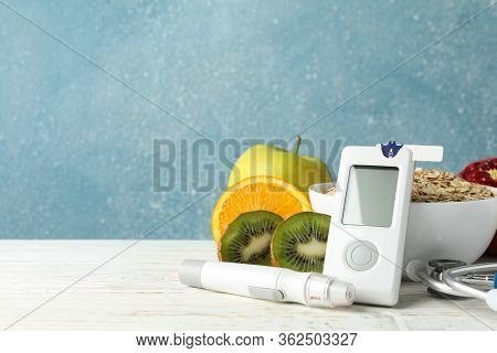 Blood Glucose Meter And Diabetic Food On Wooden Table