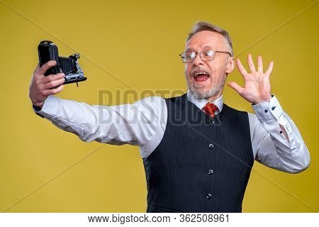 Senior Man Looking At Camera While Taking Silly Face Selfie. Waving To The Camera