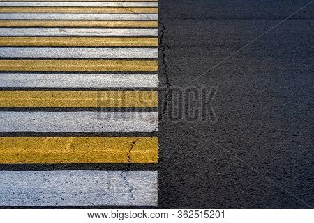 Crosswalk. Yellow And White Zebra Pedestrian Crossing And A Crack On The Road With Copy Space