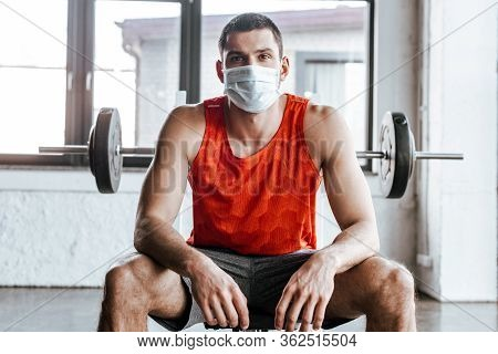 Athletic Sportsman In Medical Mask Sitting Near Barbell In Gym
