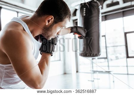 Selective Focus Of Athletic Sportsman In Boxing Gloves Training With Punching Bag