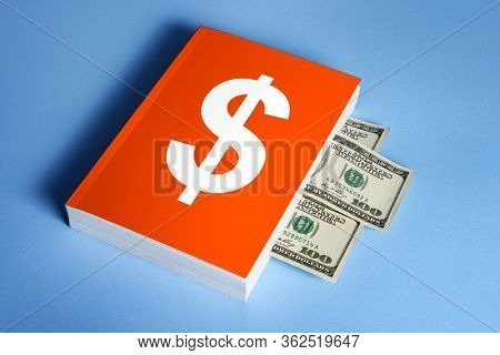 Financial literacy concept. The ability to make money and manage it. Book with dollar bills between pages