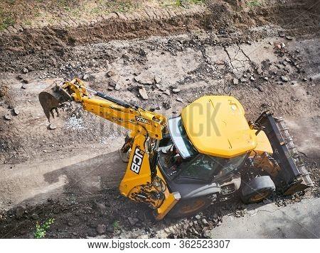 Kharkov, Ukraine - March 2020, Buldozer Is Reconstructing Asphalt Road Near The Civil Building. Hydr