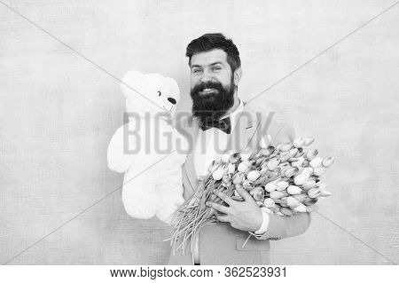 Man Bearded Gentleman Suit Bow Tie Hold Teddy Bear And Bouquet. Happy And In Love. Gentleman Making
