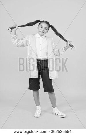 Waterproof Concept. Adorable Child. Happy Schoolgirl Wear Raincoat On Yellow Background. Small Schoo