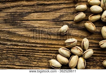 Pistachios Scattered On The Wooden Vintage Table. Pistachio Is A Healthy Vegetarian Protein Nutritio