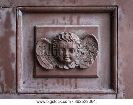 Abstract Angel On Brown Old Wooden Door. Cherub Decorates The Door Of The Catholic Church