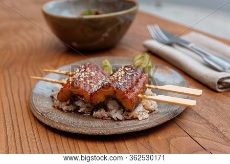 Fried unagi eel with barbecue sauce and rice in clay plate on restaurant table