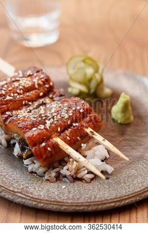 Fried unagi eel with barbecue sauce and rice in clay pale