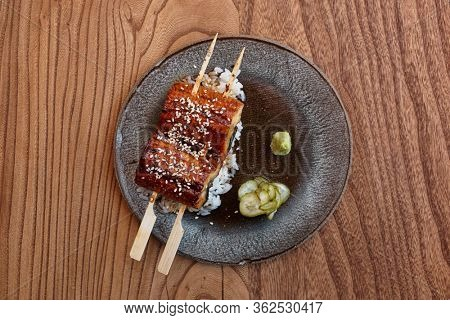 Fried unagi eel with barbecue sauce and rice shot from above on wooden table